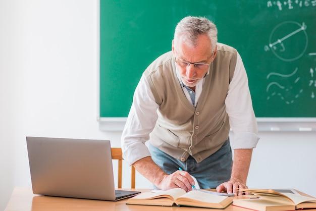 Hogere wiskundeleraar die met pen schrijven terwijl status tegen bord Gratis Foto