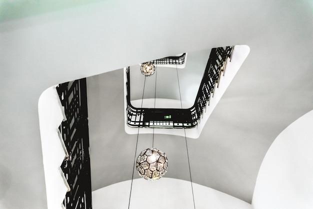 Hol van een binnentrap van een oud gebouw met witte muren en zwarte traliewerk. Premium Foto