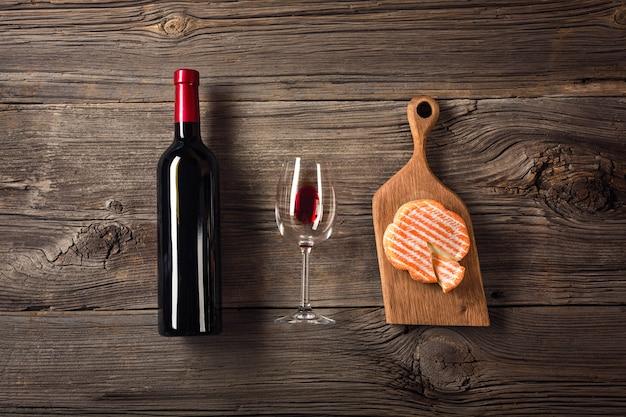 Holiday dinner setting met rode wijn en afromende kaas op rustieke hout. bovenaanzicht met ruimte voor uw groeten. Premium Foto