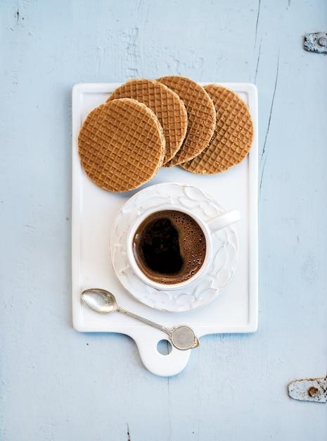 Hollandse karamel stroopwafels en kopje zwarte koffie op witte keramische serveerbord Premium Foto