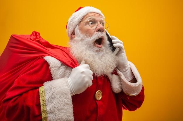 Holly jolly x mas! kerstman in hoofddeksels, kostuum, zwarte riem Premium Foto