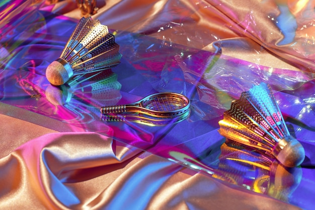 Holografische regenboog iriserende stoffen oppervlak en objecten uit de jaren 90 shuttle, racket, audiocassette, retrospectief uit de jaren 80, sportconcept. Premium Foto