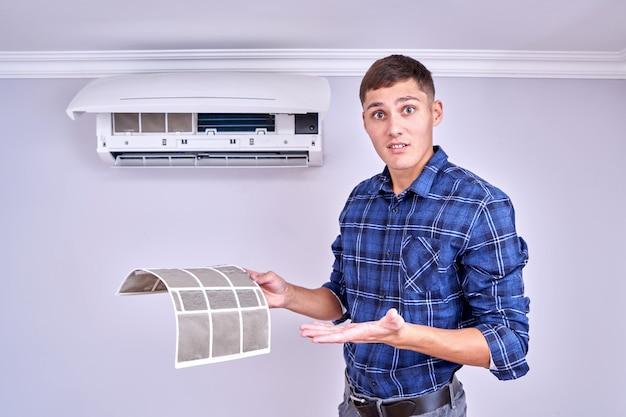 Home airconditioner vervangen en schoonmaken concept. geschokt gezicht professionele fixer toont vuile filters Premium Foto