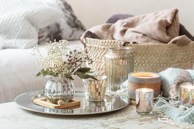 Home decoraties in het interieur. turquoise deken en rieten mand met een vaas met bloemen en kaarsen Premium Foto