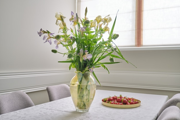 Home eetkamer interieur, lente zomer boeket bloemen, aardbeien Premium Foto