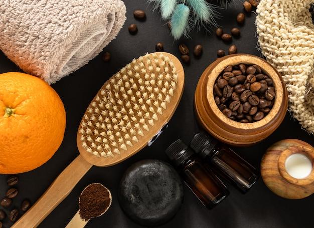 Home spa concept. body brush, stuk zeep, handdoek, sinaasappels, koffiebonen en etherische olie voor anti-cellulite massage en huidbehandeling op zwarte muur. plat ontwerp Premium Foto