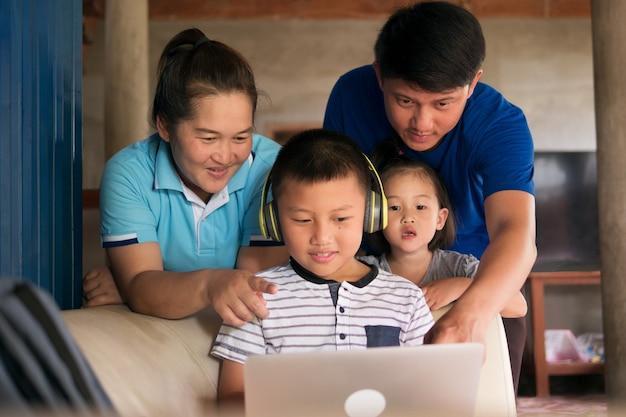Homeschooling kind jongen in hoofdtelefoon laptopcomputer gebruikt met gelukkige aziatische familie saamhorigheid in landelijk huis, ouders helpen kind met huiswerk tijdens covid-19 pandemie. Premium Foto