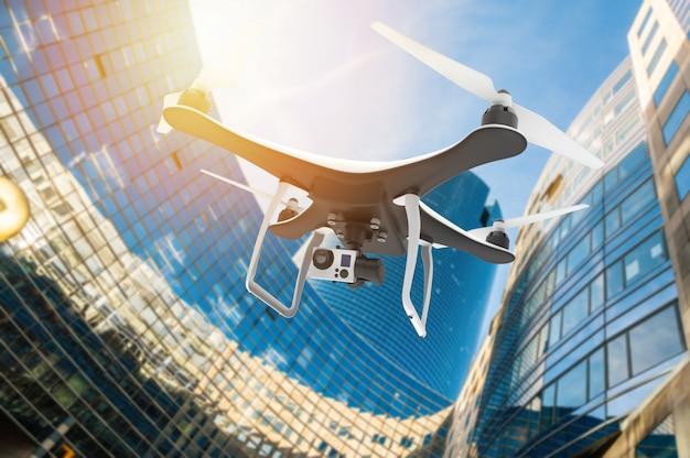 Hommel met digitale camera vliegen in een moderne stad bij zonsondergang Premium Foto