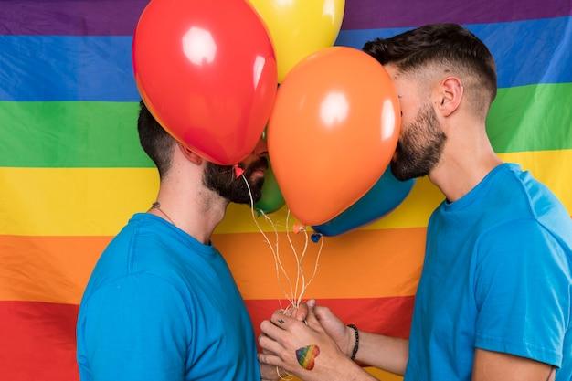 Homoseksueel paar met ballonnen op regenboogvlag Gratis Foto