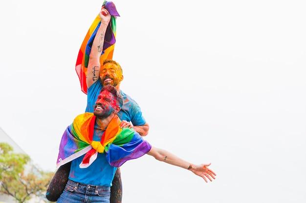 Homoseksueel paar met geschilderde gezichten die zich bij festival verheugen Gratis Foto