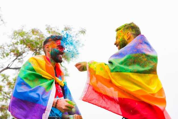 Homoseksuele mannen die elkaar besprenkelen met kleurrijk poeder Gratis Foto