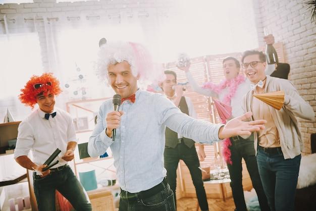 Homoseksuele mannen in kleurrijke kleding zingen karaoke op feestje. Premium Foto