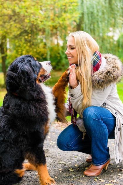 Hond die handen met poot schudt aan zijn vrouw Premium Foto