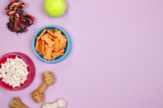 Hondentoebehoren, voedsel en stuk speelgoed op purpere achtergrond. plat leggen. bovenaanzicht. Premium Foto