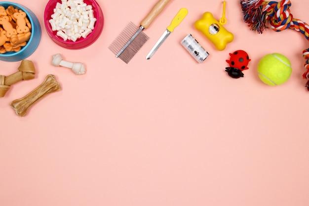 Hondentoebehoren, voedsel en stuk speelgoed op roze achtergrond. plat leggen. bovenaanzicht. Premium Foto