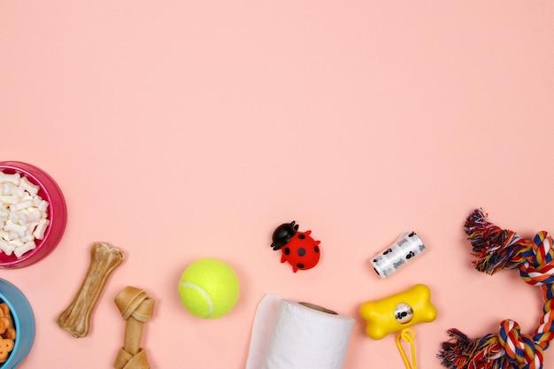 Hondentoebehoren, voedsel en stuk speelgoed op roze achtergrond. Premium Foto