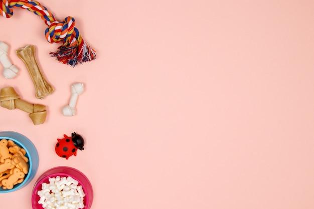 Hondentoebehoren, voedsel en stuk speelgoed op roze achtergrond Premium Foto