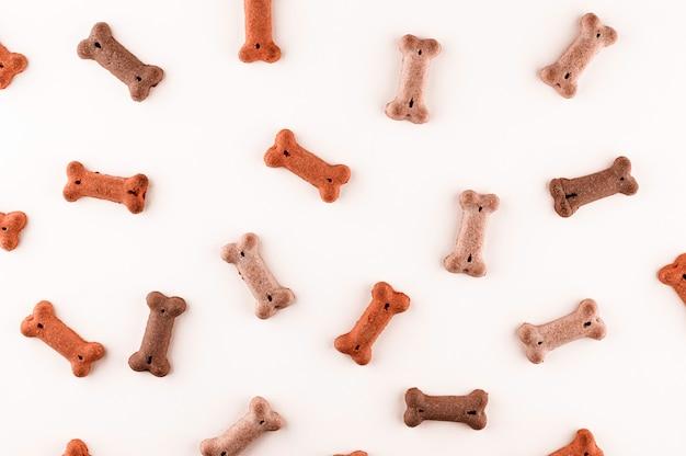 Hondenvoerpatroon gemaakt met droge snacks in de vorm van botten. grappige schattig plat lag textuur. huis huisdieren, dieren voederen. speciaal dieet, trainingsaanbod. Premium Foto