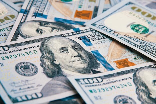 Honderd amerikaanse bankbiljetten zijn verspreid. contant honderd dollarbiljetten, dollar achtergrondafbeelding. Premium Foto