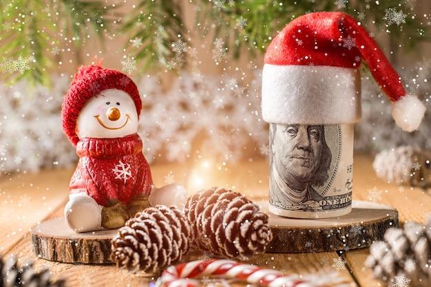 Honderd dollar biljet met sneeuwpop in een rode dop Premium Foto