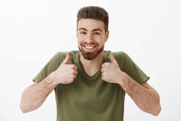 Honderd procent ja. portret van opgewonden gelukkig vrolijke aantrekkelijke bebaarde blanke man in t-shirt duimschroef opwaarts in goedkeuring en als gebaar vrolijk en ondersteunend goed idee accepteren Gratis Foto