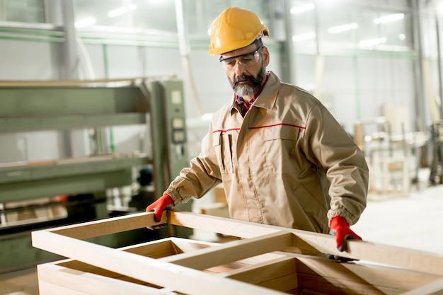Honderdjarige arbeider van middelbare leeftijd die in de meubelfabriek werkt Premium Foto