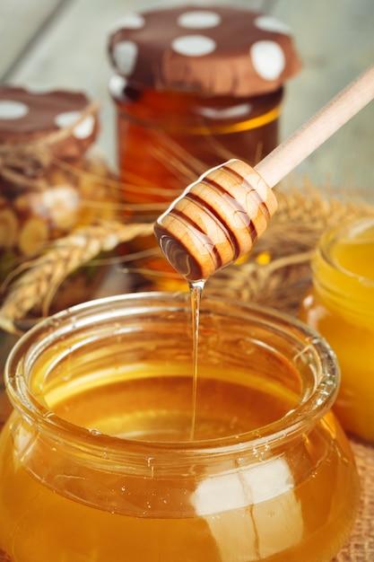 Honey achtergrond. zoete honing in glaskruik op houten achtergrond. Premium Foto
