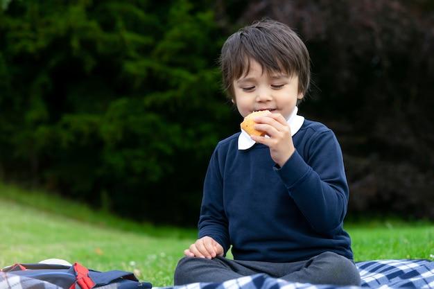 Hongerige kleine jongen die verse tortilla-wraps eet met kip, spek en gemengde groenten, schattige schooljongen die een picknick in het park heeft, kind dat mexicaans sandwich-eten eet voor zijn diner Premium Foto