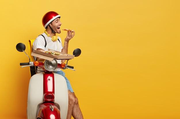 Hongerige knappe mannelijke bestuurder op autoped met rode helm die pizza levert Gratis Foto