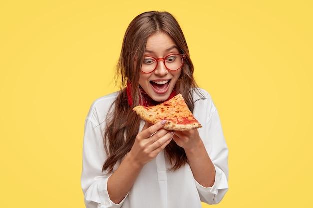 Hongerige student opent mond wijd terwijl hij een heerlijk stuk pizza ziet, wil eten, gekleed in wit overhemd, modellen tegen gele muur. positieve vrouw met ongezonde kost. mensen en eten Gratis Foto