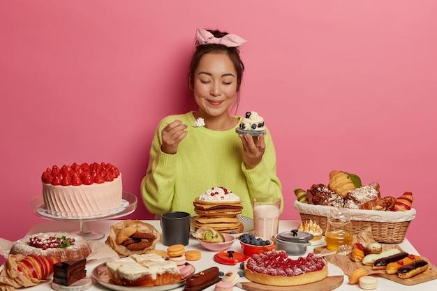 Hongerige zoetekauw meisje houdt cupcake in de ene hand, lepel met room in andere, krijgt portie suiker geniet van heerlijke snack tijdens feestelijke gebeurtenis houdt de ogen gesloten van plezier. Gratis Foto