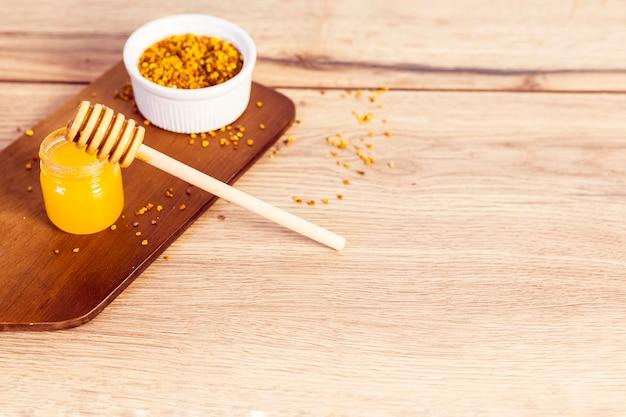 Honing en bijenstuifmeel op houten geweven Gratis Foto
