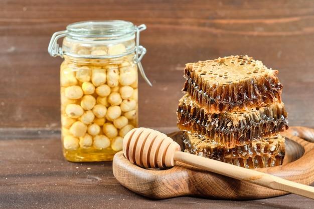 Honing in honingraten op een houten plaat en gouden honing in potten met noten Premium Foto