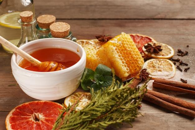 Honing, kaneel en gedroogde vruchten op een houten tafel. gezond eten. Premium Foto