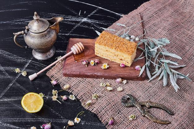Honingcake op een houten bord met gedroogde bloemen en theepot. Gratis Foto
