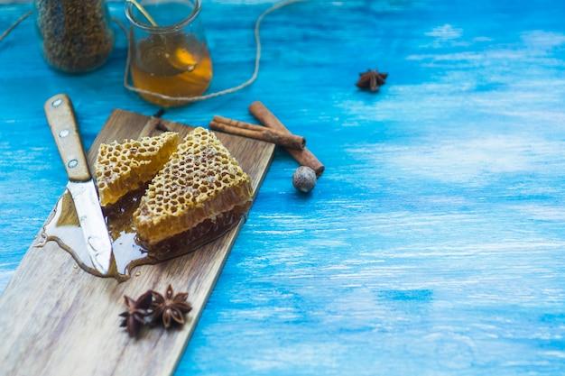 Honingkamstukjes met kruiden; bee pollens jar; mes en honing pot op blauwe achtergrond Gratis Foto