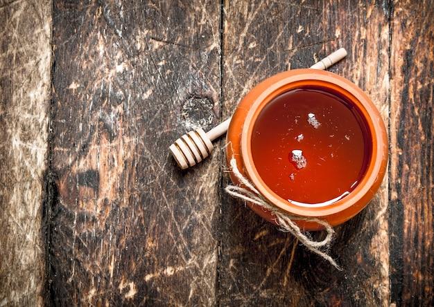 Honingpot met een houten lepel op houten tafel. Premium Foto