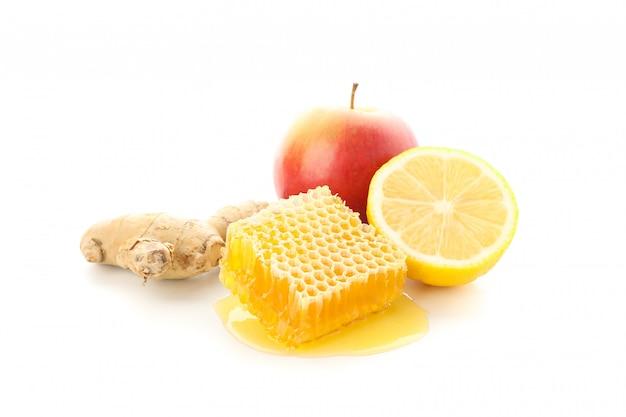 Honingraat, appel, citroen en gember geïsoleerd op een witte achtergrond Premium Foto