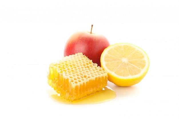 Honingraat, appel en citroen geïsoleerd op een witte achtergrond Premium Foto