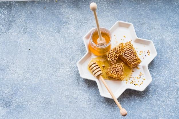 Honingraatstukken met honingkruik in wit dienblad op geweven achtergrond Gratis Foto