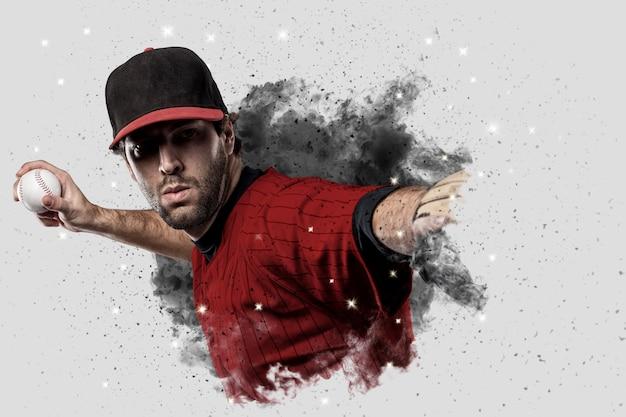 Honkbalspeler met een rood uniform dat uit een rookstoot komt. Premium Foto