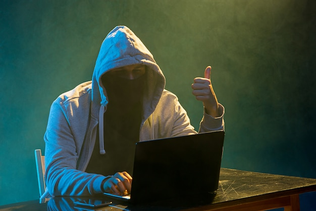 Hooded computerhakker die informatie met laptop steelt Gratis Foto