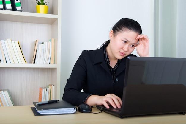 Hoofdpijn aziatische zaken vrouw houdt haar hoofd, werken met laktop Premium Foto