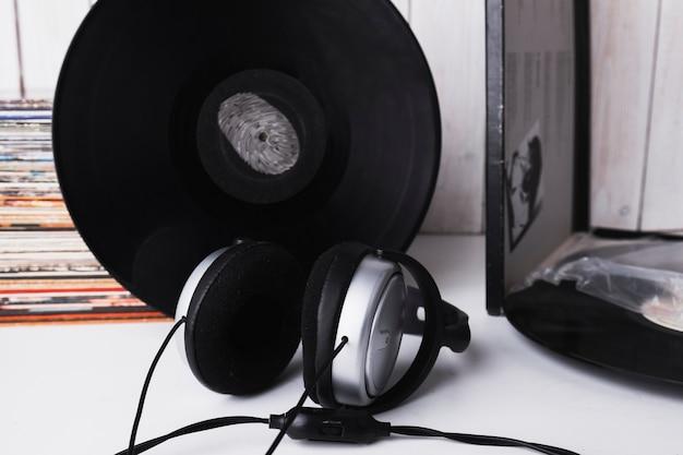 Hoofdtelefoon dichtbij vinylschijf met vingerafdruk Gratis Foto