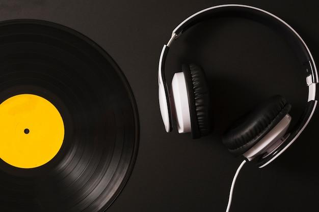Hoofdtelefoon en uitstekend vinylverslag op zwarte achtergrond Gratis Foto