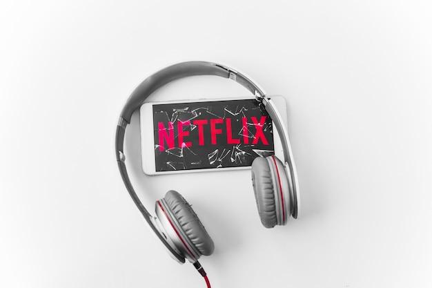 Hoofdtelefoon in de buurt van kapotte smartphone met netflix-logo Gratis Foto