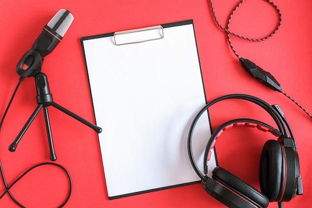 Hoofdtelefoon, microfoon en klembord met wit papier op rode achtergrond. conceptmuziek of podcast. bovenaanzicht, plat lag Premium Foto