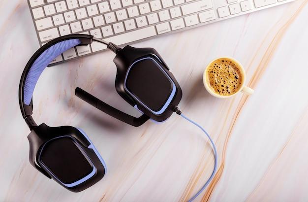 Hoofdtelefoon op de tafel bij het toetsenbord in het callcenter en technische ondersteuning bij een kopje koffie Premium Foto
