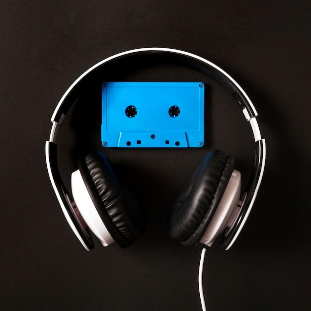 Hoofdtelefoon over de blauwe cassetteband op zwarte achtergrond Gratis Foto