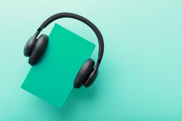 Hoofdtelefoon wordt gedragen op een boek in een blauwe hardcover op een blauwe achtergrond, bovenaanzicht. Premium Foto